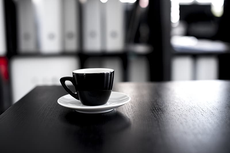 Black teacup on white saucer over table