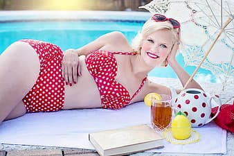 Woman in red and white polka dot dress sitting on white textile