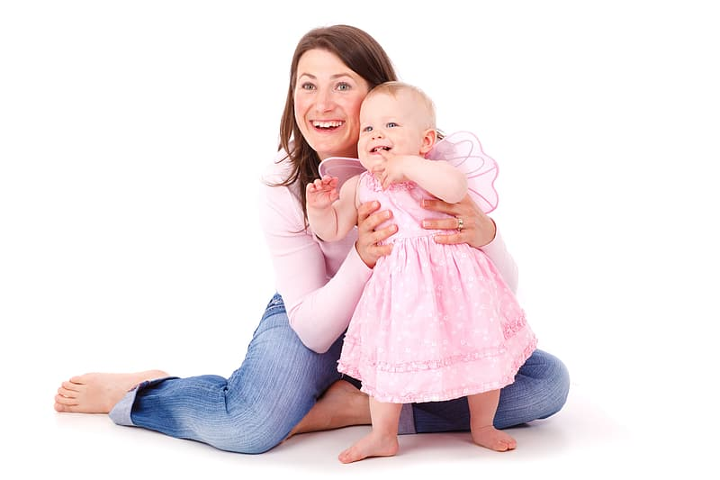 Woman in pink long-sleeved top and blue jeans sitting on floor with infant in pink dress