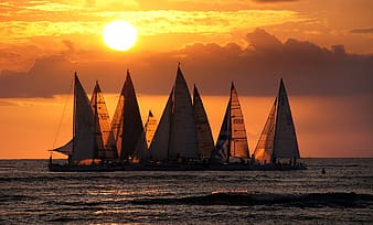 Group sailing boat on body of water during sunset