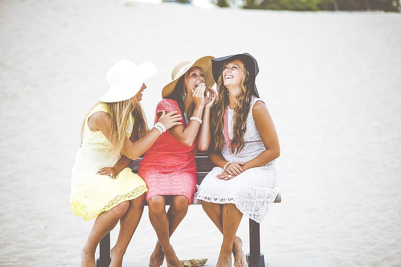 Three women with assorted-color dresses sitting on bench beside seashore