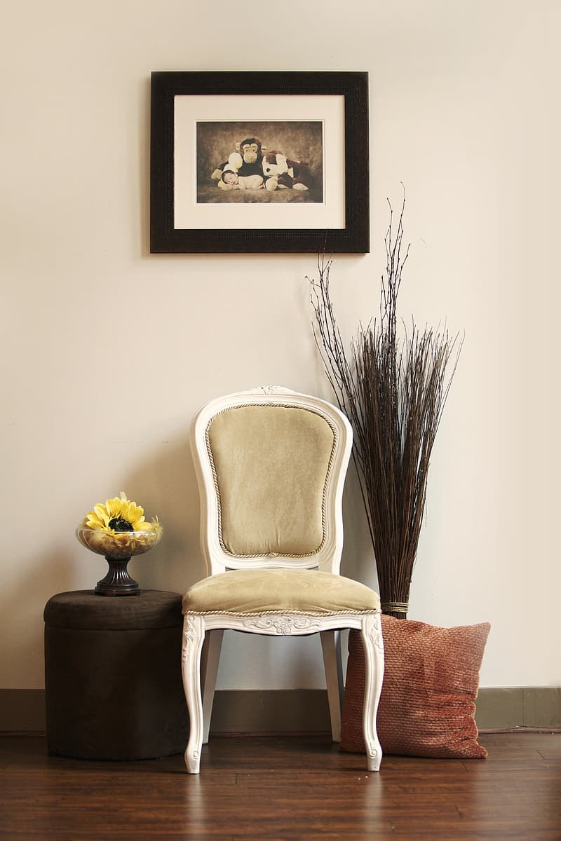 White wooden framed padded chair under painting with framed hanged on wall