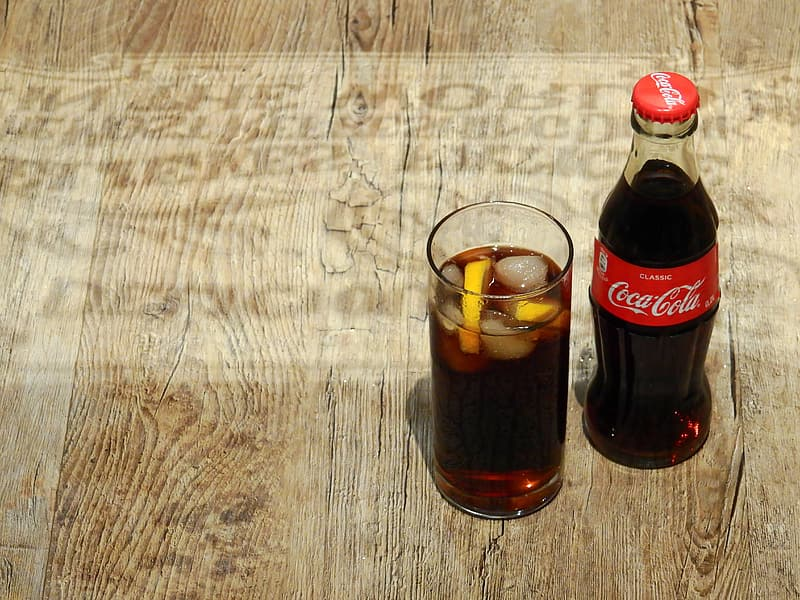 Coca-Cola glass bottle beside highball glass with beverage