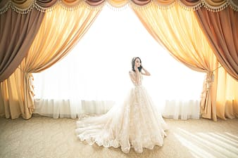 Woman in white wedding dress standing on white carpet