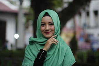 Woman in green hijab covering her face with her hand