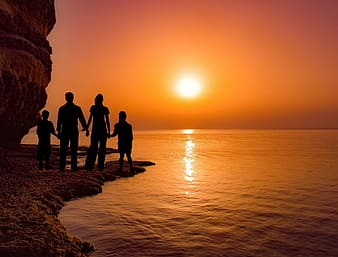 Silhouette photography of family standing on shore