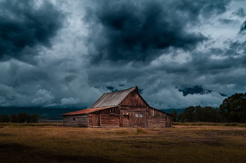 Brown wooden house under cloudy sky