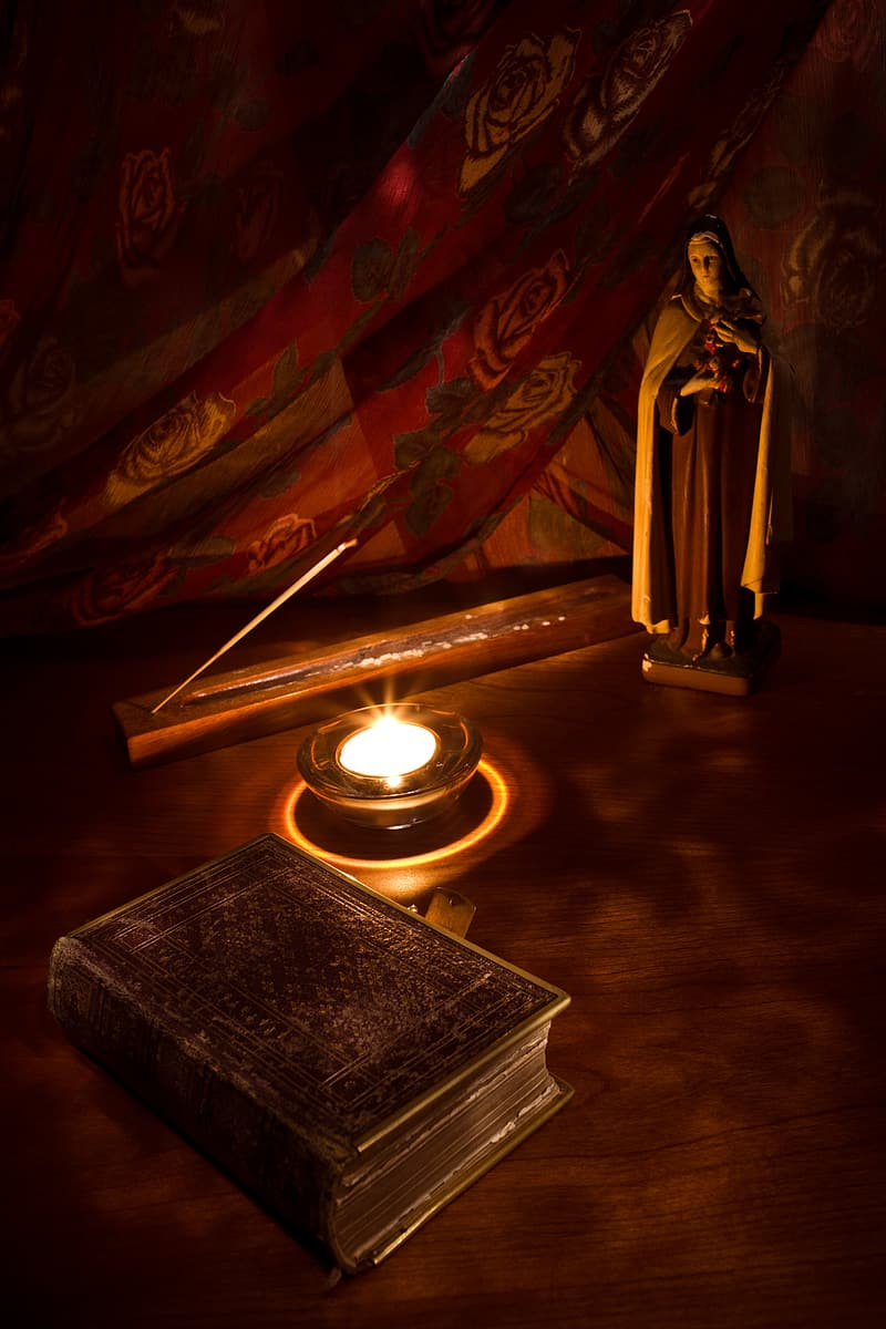 Religious figurine near lighted candle and book on brown table