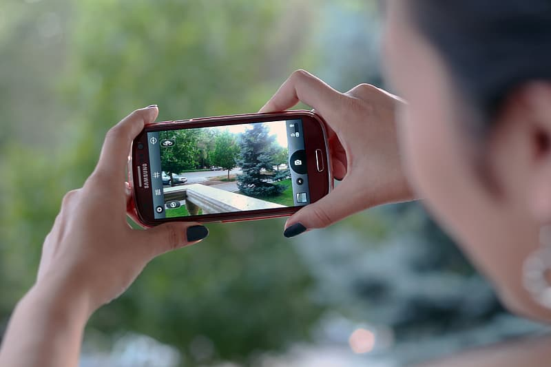 Woman taking picture using red Samsung Android smartphone