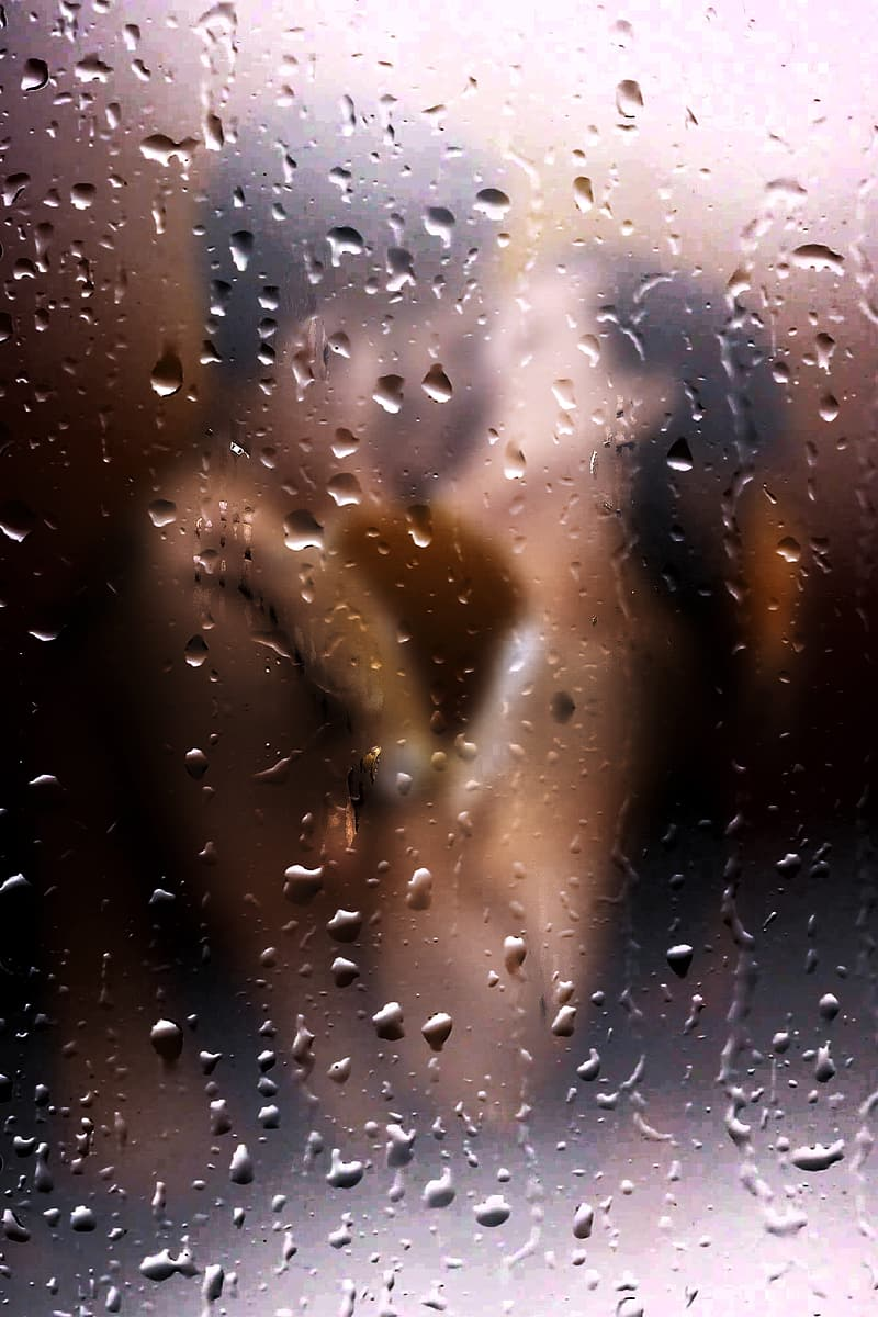 Couple kissing behind glass