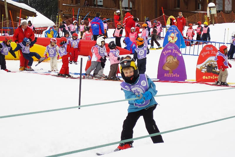 Toddler learning how to ski at daytime