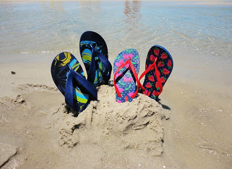 Two pairs of blue and pink flip-flops on sand