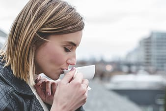 Close up photo of person sipping white teacup