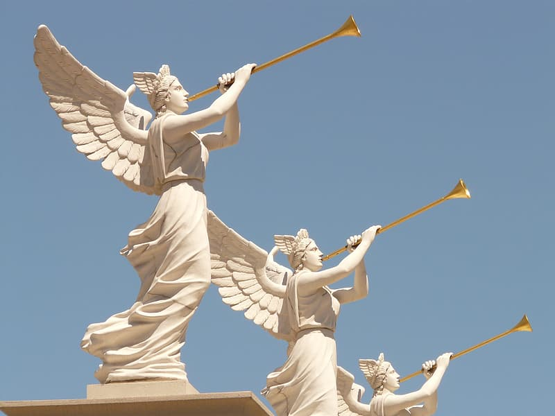 Three white painted concrete Angel playing trumpets during daytime