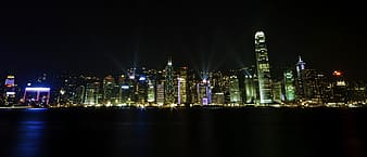 Panorama photography of lighted high-rise buildings nearby sea