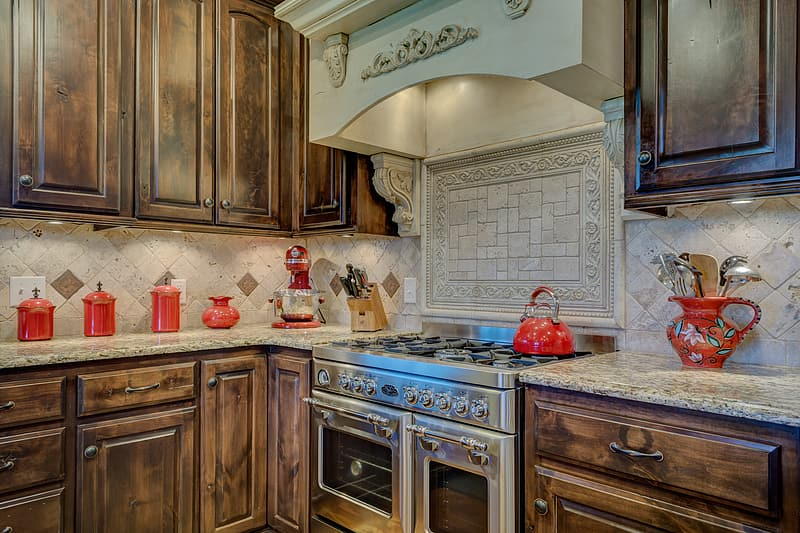 Red ceramic jar on countertop near silver gas range oven