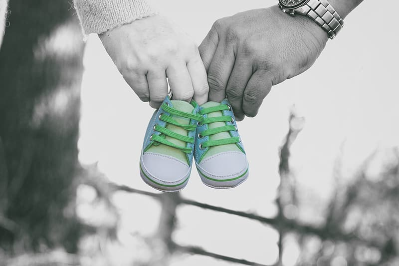 Selective color photo of man and woman holding white-and-gray baby shoes
