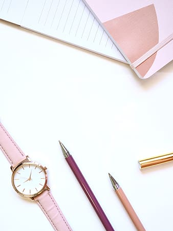 Pink and silver click pen beside white round analog watch