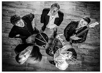 Grayscale photography of five man looking up holding guitars and drum
