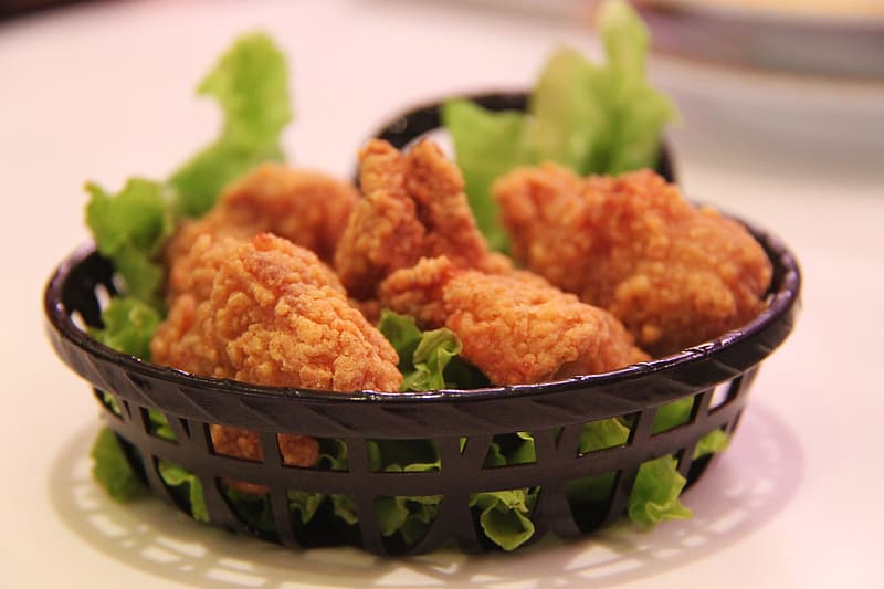 Fried chicken with letus in round black mesh plate