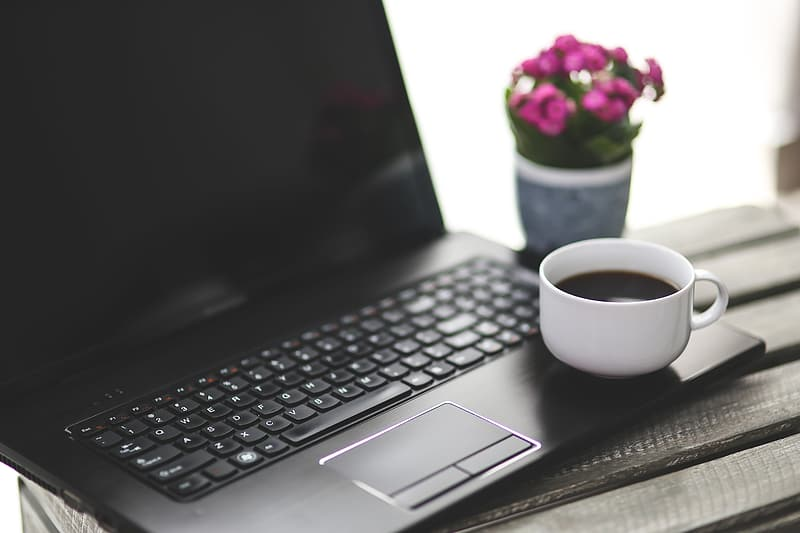 White teacup on black laptop computer