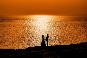 Silhouette of 2 people standing on rock formation near body of water during sunset