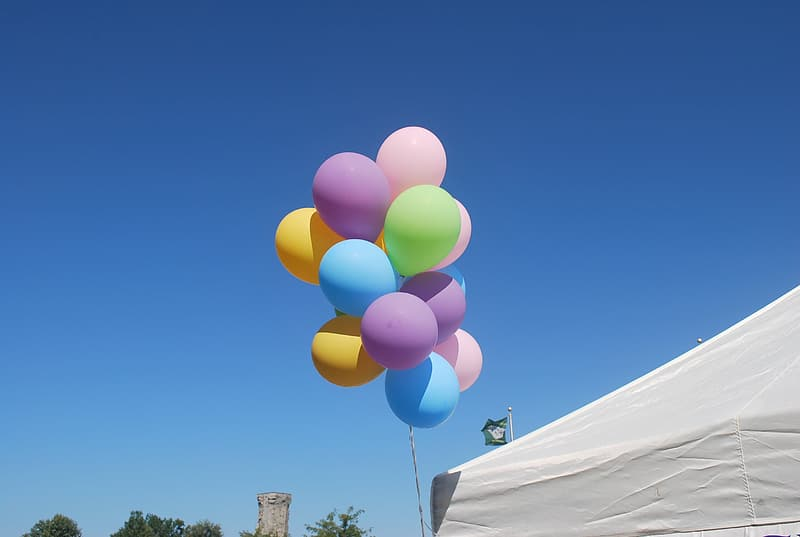 Assorted-color balloon beside white tent during daytime