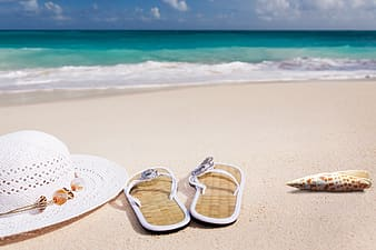 Pair of beige-and-white flip-flops beside white hat on seashore during day