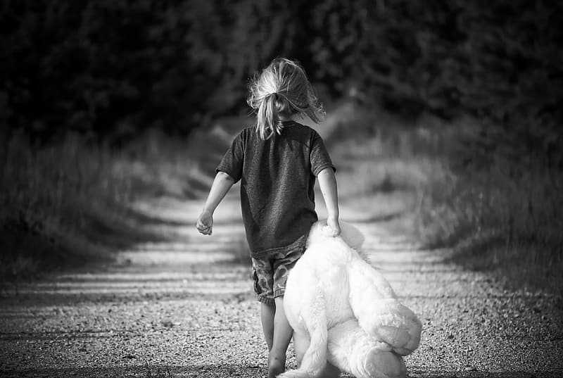 Grayscale photo of girl wearing t-shirt holding teddy bear