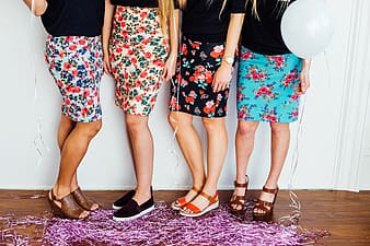 Four person in floral skirts standing beside white wall