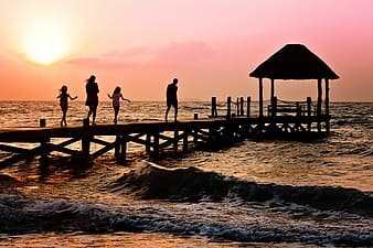 Photography of silhoutte of four persons walking on sea dock