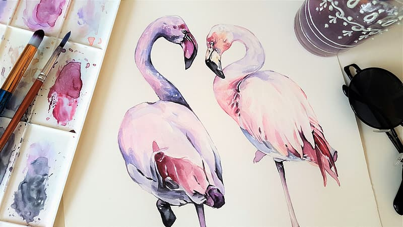 Purple and pink flamingo paintings beside paint brushes