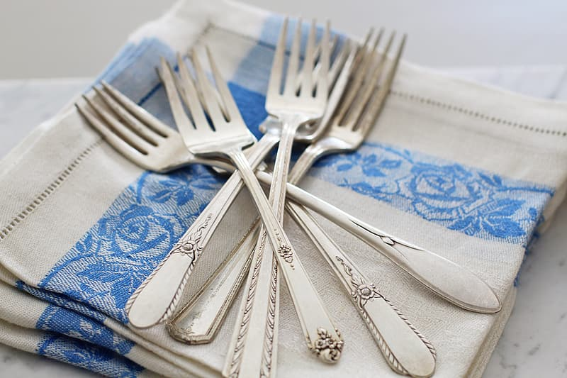 Silver fork and bread knife on blue and white textile