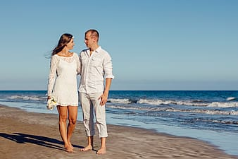 Woman in lace long-sleeved mini dress with man in white dress shirt standing on seashore during daytime