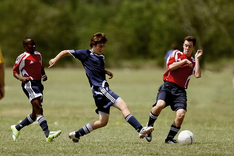 Three male playing soccer