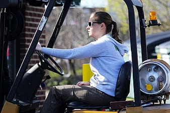Closeup photo of woman operating forklift during daytime