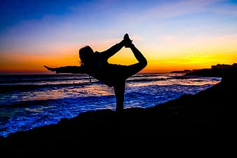 Silhouette photo of woman doing yoga during sunset