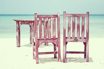 Two red wooden chairs on shore at daytime