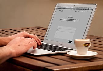Person using MacBook Air while having coffee