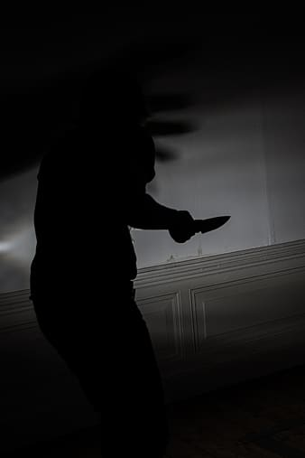 Photograph of silhouette person holding a knife