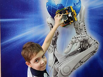 Boy in white and black suit holding blue and white robot toy