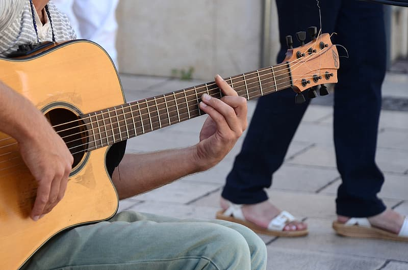 Shallow focus photography of man using brown cutaway acoustic guitar