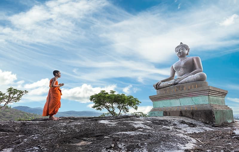 Man praying in front of Gautama Buddha statue