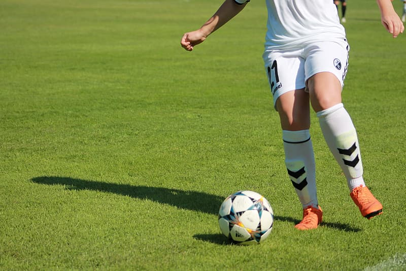 Person in white soccer jersey kicking soccer ball on green grass field during daytime