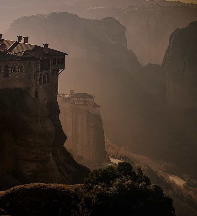 White and brown concrete building on cliff