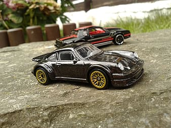 Two black and red toy cars on rock