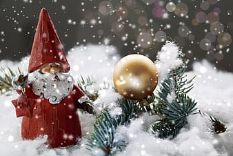 Santa Claus figure on snowfield beside gold-colored ornament