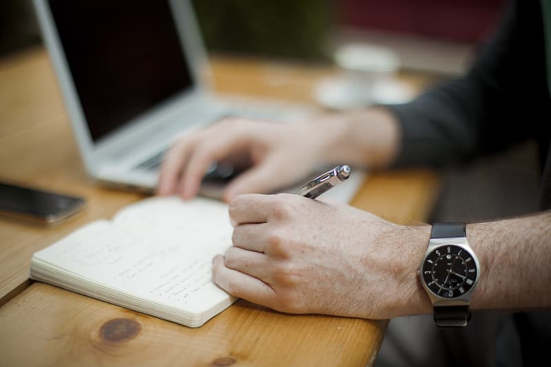 Person wearing silver link bracelet round analog watch and using macbook