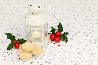 White candle lantern near the chrysanthemum and cookies