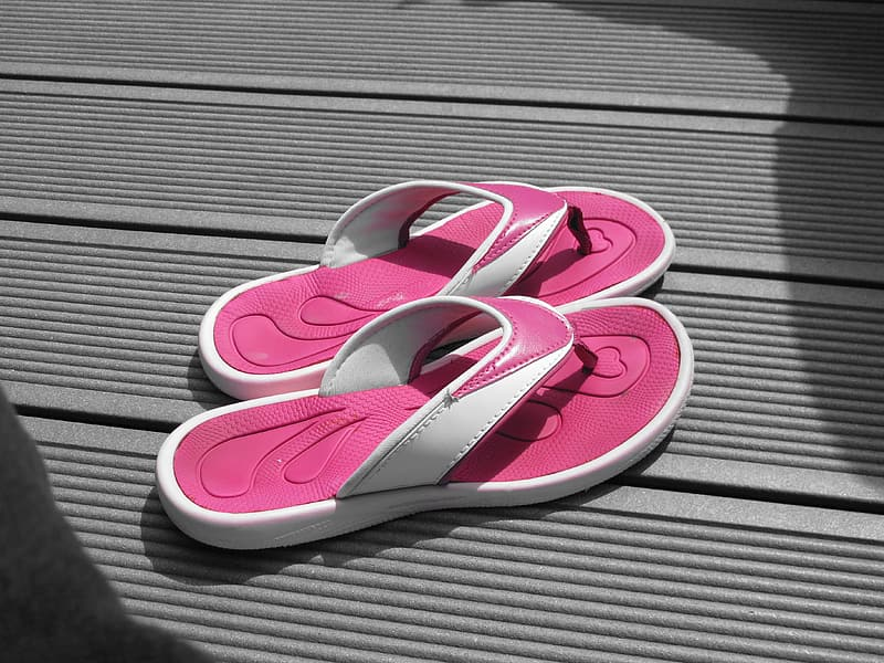 Pair of pink-and-white flip-flops on floor